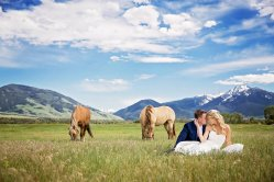 bride and groom in a field with horses and mountain views, blue skies