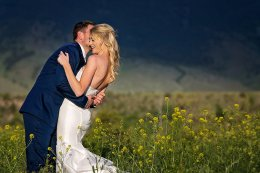 bride and groom embrace in a field of wild flowers
