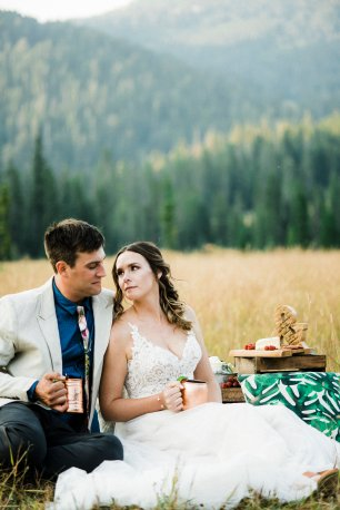 bride and groom at weddng picnic, sharing drink