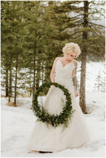 bride in gown holding floral wreath, winter wedding
