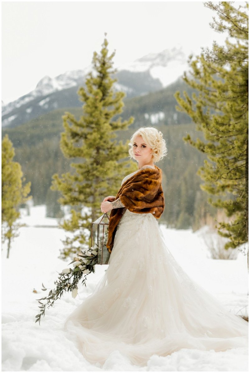 winter wedding, bride in gown with faux fur shawl, holding floral lantern