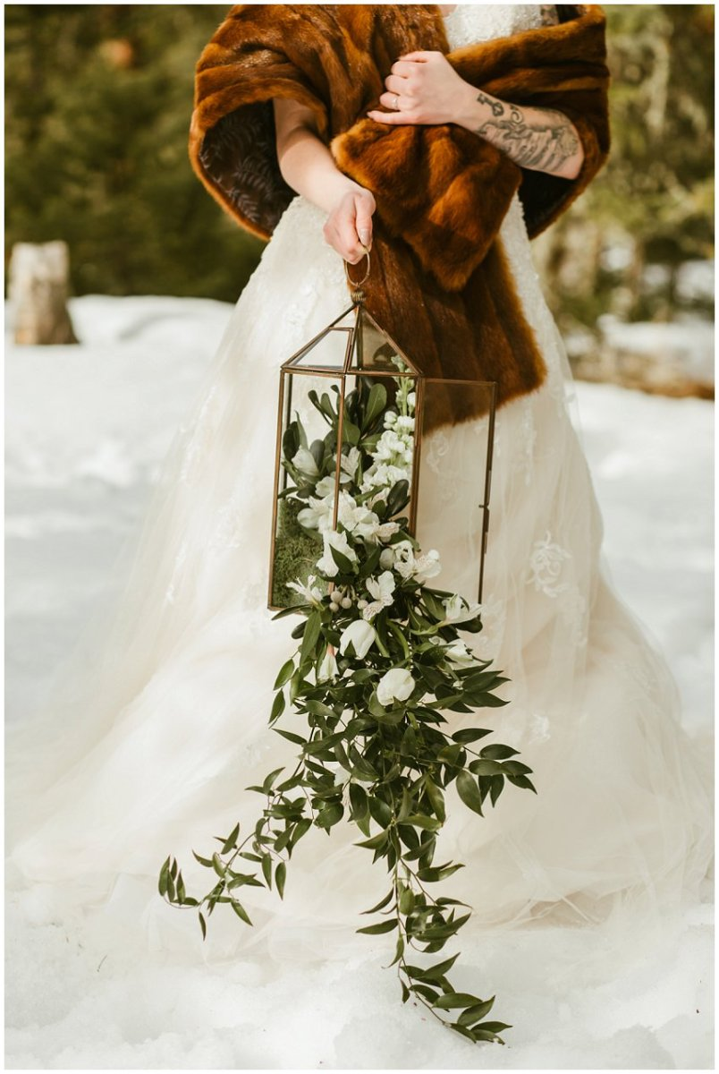 winter wedding, bride in faux fur shawl, holding floral lantern