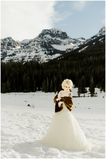 winter wedding bride in gown with fur shawl, snow covered mountains