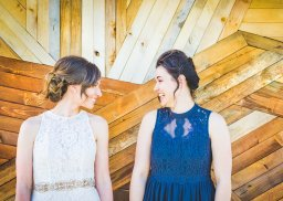 bride and maid of honor laughing in front of unique wooden building