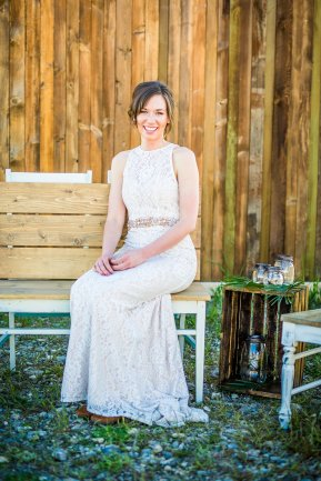 bride sitting on bench, simple vitange crates and jars decor with greenery