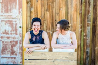 bride and maid of honor laughing, leaning on handcrafted wooden bench