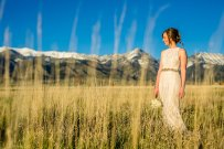 bride with bouquet standing in a field with snow capped mountains in the background