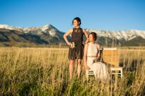 bride and maid of honor in a field with a hand crafted wooden benches, snow capped mountains in the background