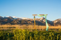 wedding arch, draped with teal fabric and decorated with eucalyptus and white roses, set up in a field of wild flowers with snow capped mountains in the background