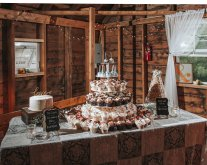 wedding dessert buffet table with cake, cupcakes, and cookies
