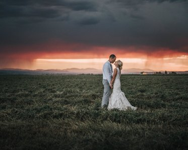 bride and groom sunset photo with rain and storm in the background