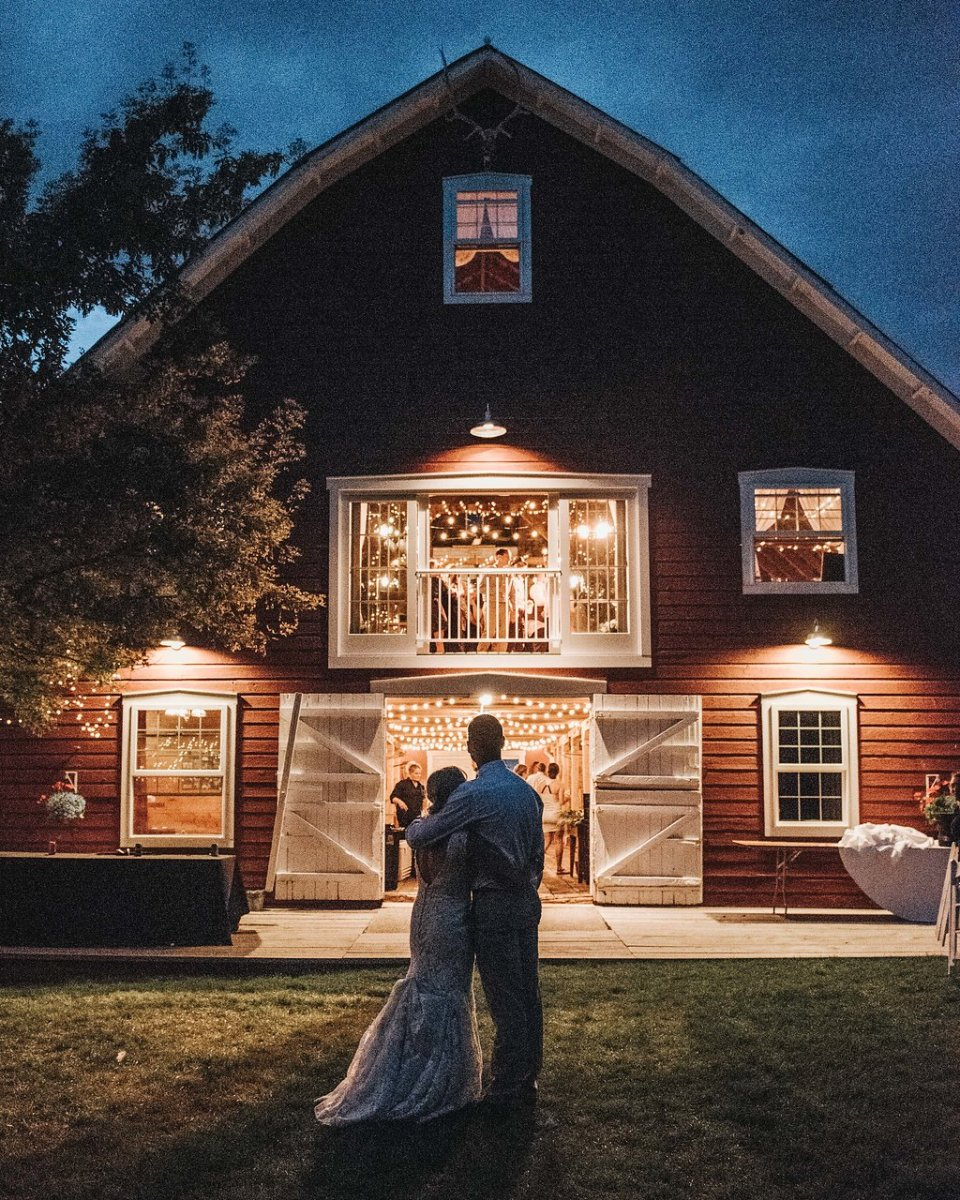 bride and groom standing in front of historic barn at night