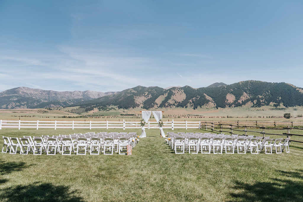 wedding ceremony with arch, fabric draping and floral, mountain views
