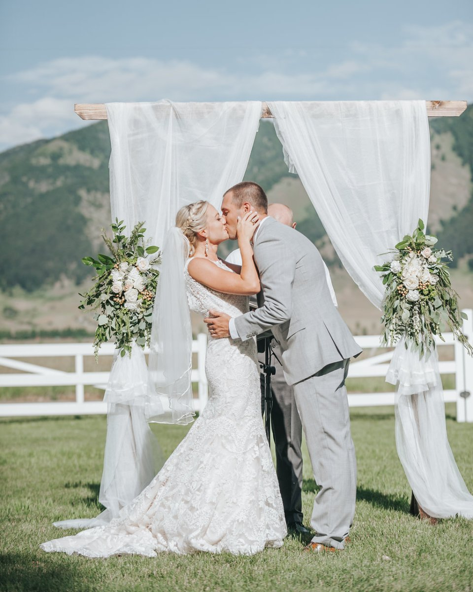 bride and groom share first kiss, draped wedding arch with flowers, mountain views