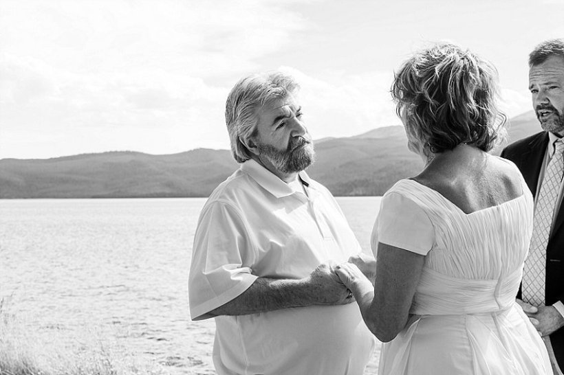 husband and wife exchange vows, vow renewal on Hebgen Lake