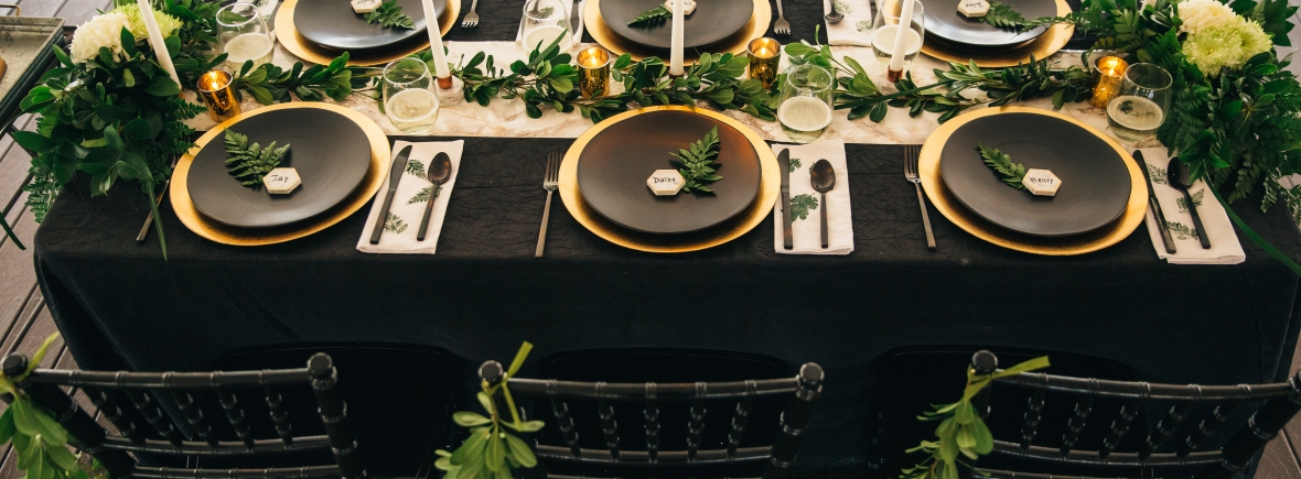 intimate wedding tablescape in black, green, and gold with marble accents
